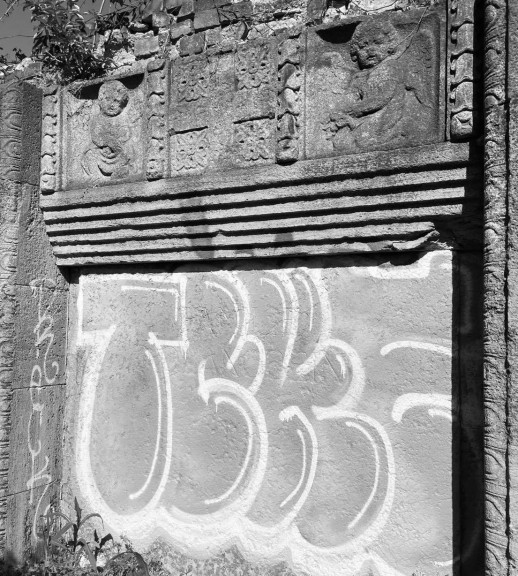 Surviving northern memorial wall with cherubs and a cross, Friedenspark, Leipzig