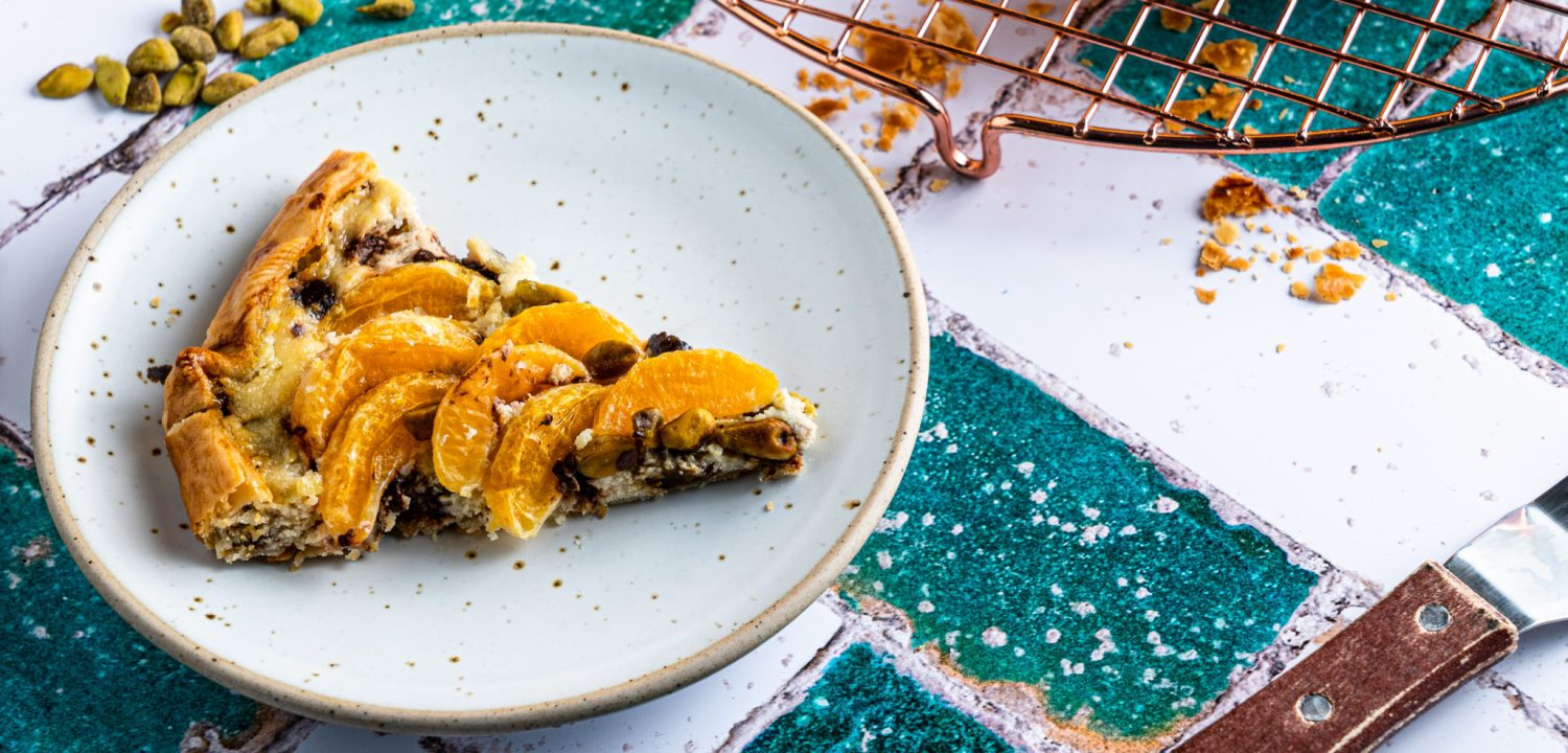 A slice of decadent tangerine, chocolate chip and pistachio cannoli galette waiting to be devoured.