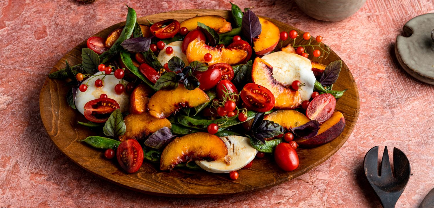 A lush summer salad with peaches, tomatoes, green beans, basil, balsamic vinegar and olive oil.