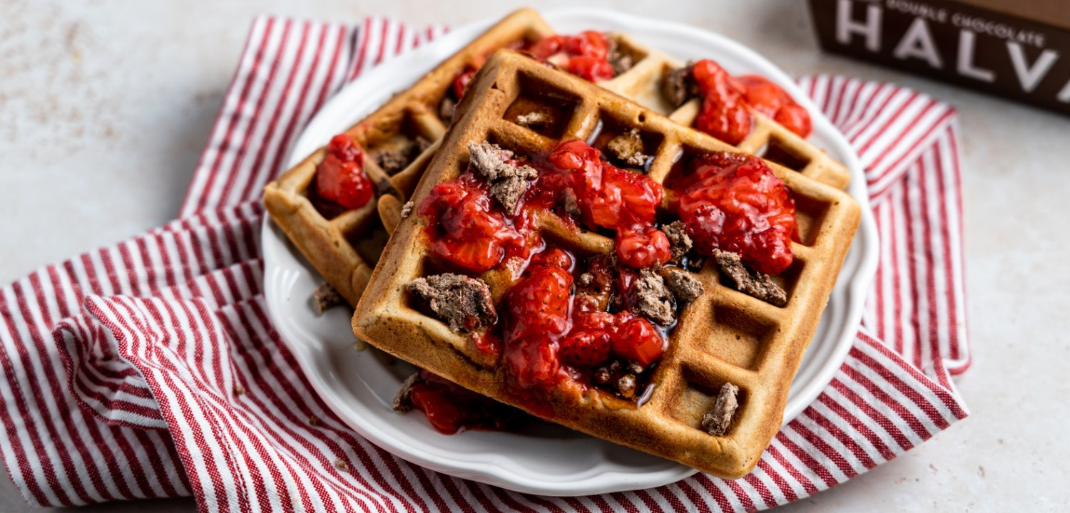 A header shot of tahini waffles with crumbled chocolate halva and strawberry compote