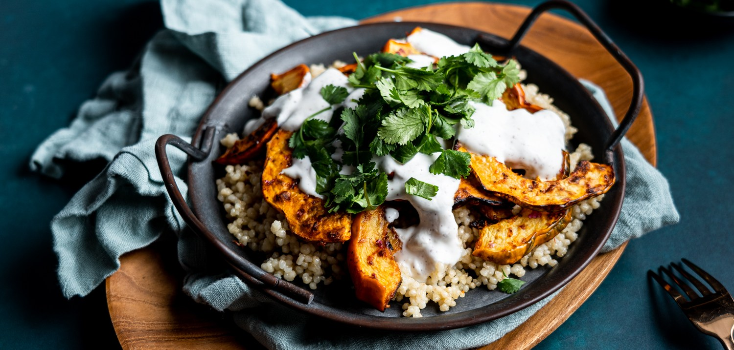 A header shot of harissa roasted acorn squash over a bed of couscous. It's topped with a garlicky sumac yogurt sauce and some fresh cilantro!