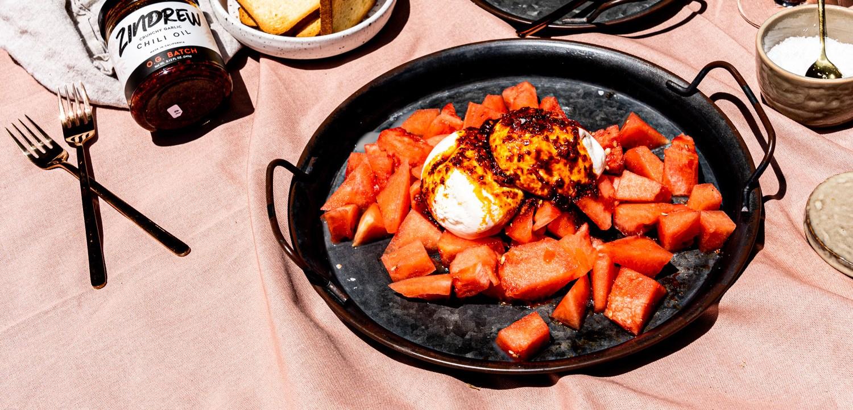 A picnic spread with a platter of watermelon, burrata and chili crisp.