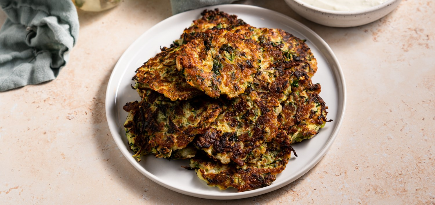 A header shot of a plate of zucchini and halloumi fritters.