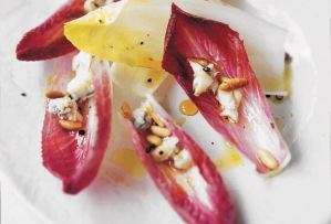 Leaves of endive salad with gorgonzola, pine nuts, and honey scattered on a white plate.