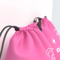 close up of our PP non-woven reusable drawstring bag closure, on a hot pink material with a one colour logo print
