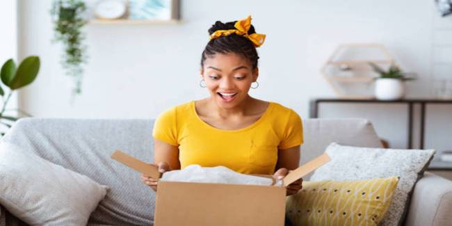 A woman in a yellow shirt opens a box with a surprised look on her face