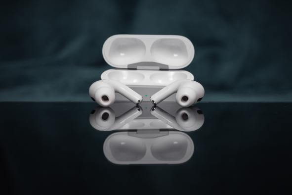 Airpods pro out of the case with a reflection showcasing apples unique packaging.