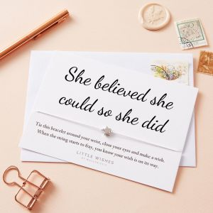 """White carded bracelet with font that reads """"She believed she could so she did"""""""