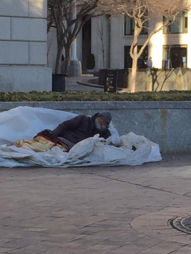 """This image shows a homeless man, in the Winter of 2018 laying on the concrete sidewalk on top of a plastic """"lean-to."""""""