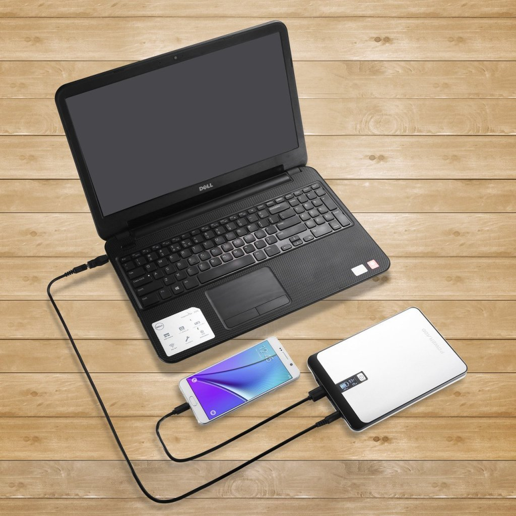 A laptop that is being charged with poweradd pilot pro2 power bank