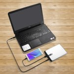 A laptop that is being charged with a power bank