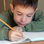 boy focussed on writing in notebook