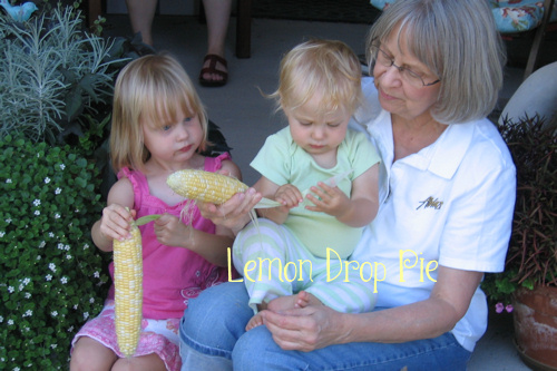 Mom husking corn with Lily and Emmy.