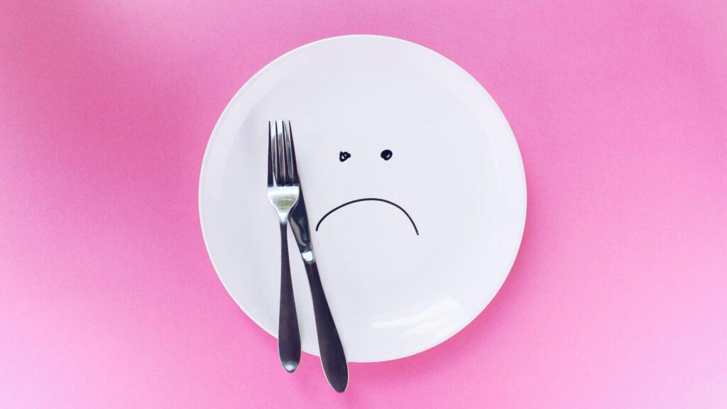Teller auf den ein trauriges Gesicht gezeichnet ist, mit Gabel und Messer auf pinkem Hintergrund von oben. Aus dem Artikel Intervallfasten Pro und Contra