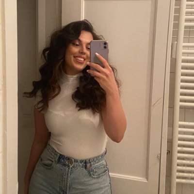Junge Frau mit braunen langen Haaren trägt ein weißes Oberteil und eine hellblaue Momjeans und macht ein Spiegelselfie. Aus dem Artikel: Wir fordern, dass der Frauentag 365 Tage im Jahr ist.