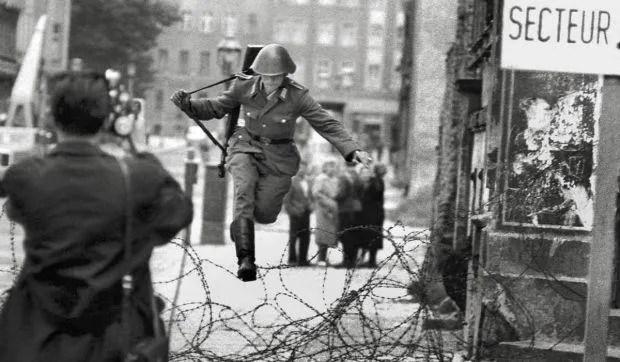 foto storica del soldato della DDR Conrad Schumann mentre salta sul filo spinato del muro di Berlino