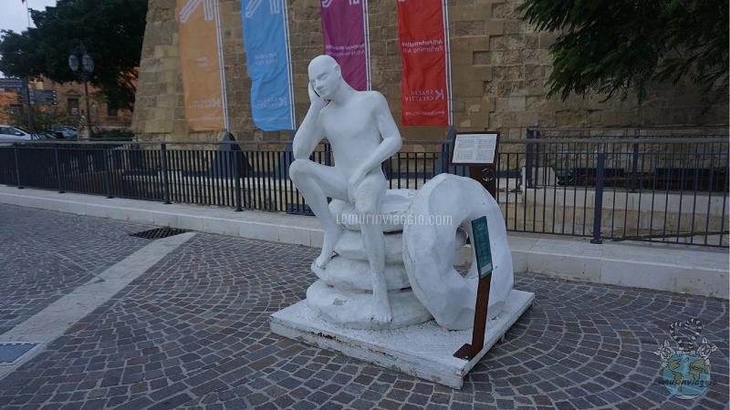 Statua dell'uomo sulle ciambelle a La Valletta, Malta. Rappresenta il proverbio chi va a dormire affamato sogna pane