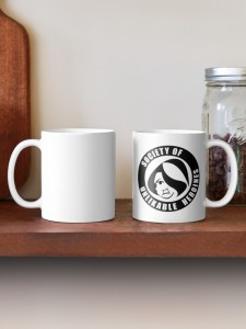 Wooden shelf, upon which sits a mug emblazoned with the Society of Unlikable Heroines logo