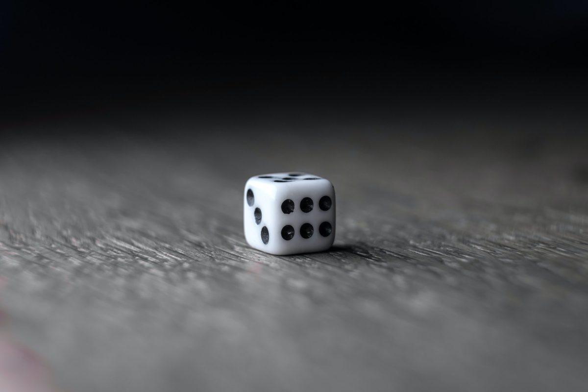 Nahaufnahme eines weißen, sechsseitigen Würfels auf einem Holztisch. Die Ziffern sechs und drei sind vorne zu sehen.