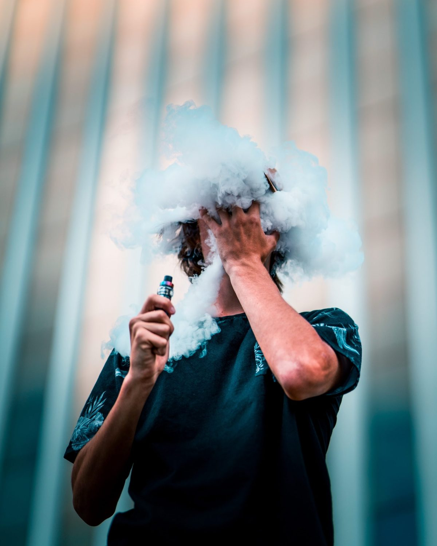 Junger Mann im schwarzen T-Shirt dampft mit E-Zigarette und vernebelt damit sein Gesicht.