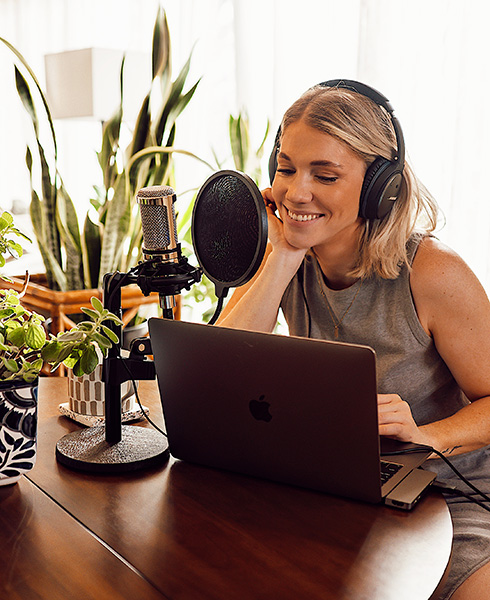 Lena sitting at a computer hosting her podcast called hometown earth