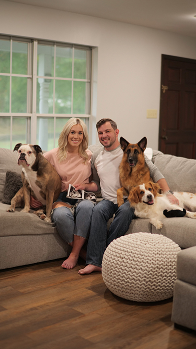 woman and man sitting with their dogs
