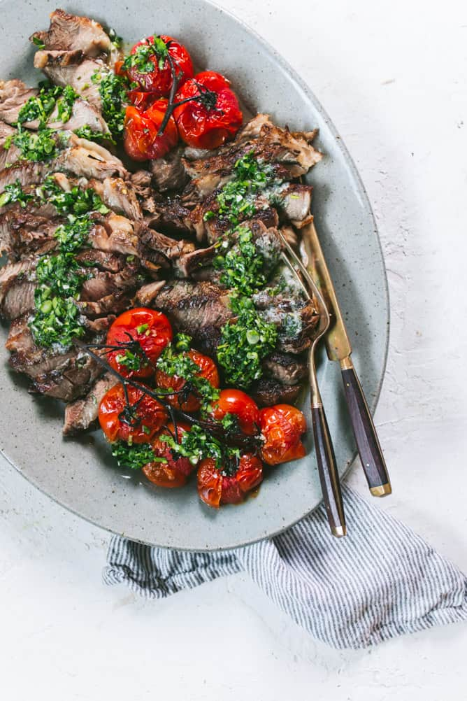 Easy rib eye steak cooked in the oven served with compound butter, roasted tomatoes, and chimichurri sauce