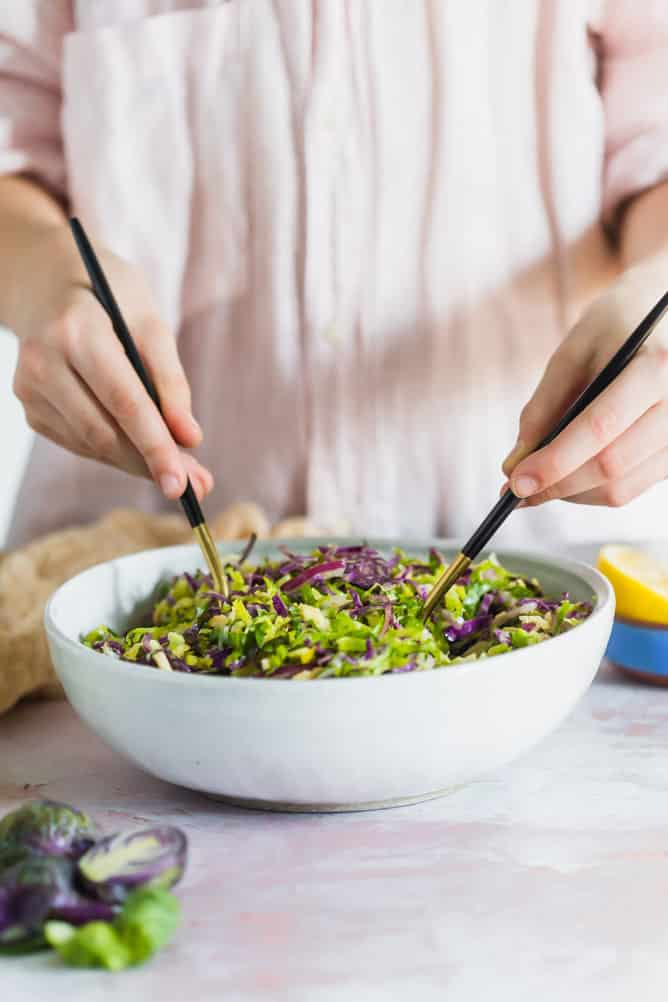 Tossing shaved brussels sprouts salad with black and gold forks