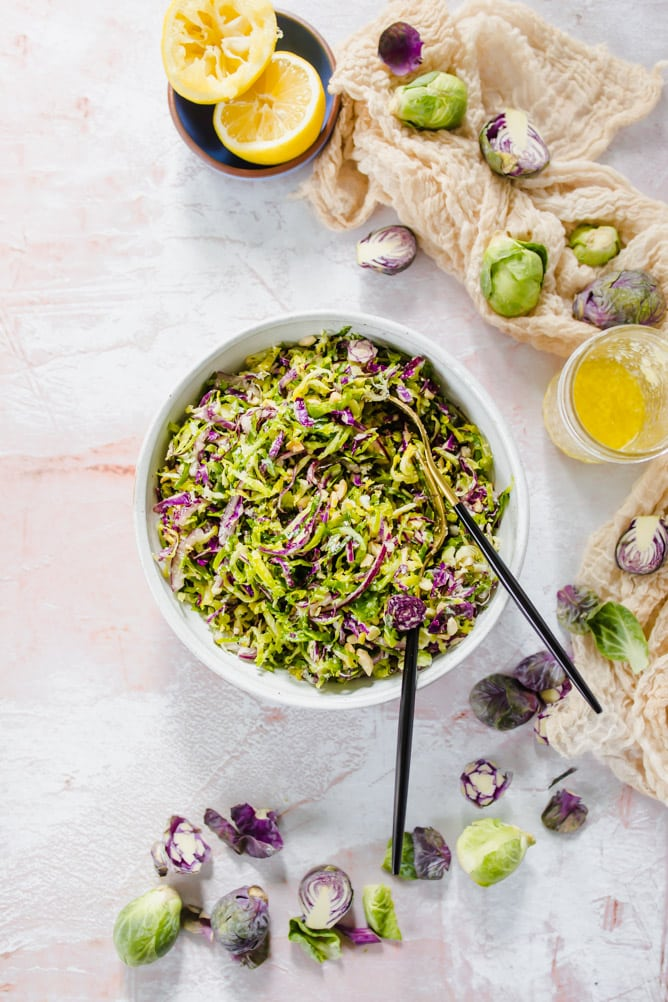 brussels sprout salad in white bowl with black adn gold forks with sprouts and dressing on the side