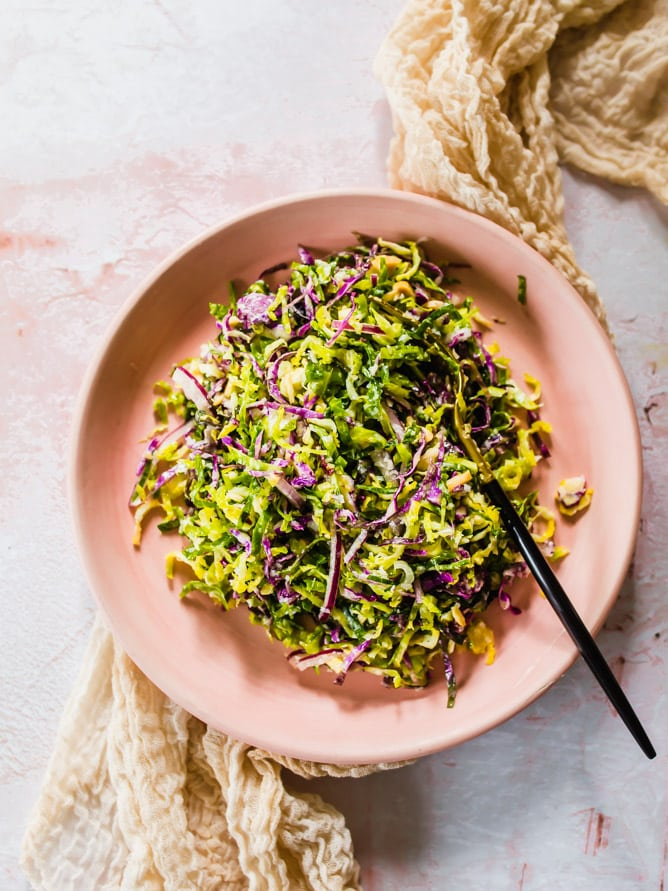 raw brussels sprout salad with parmesan cheese, red onions, almonds and citrus dressing in pink bowl.