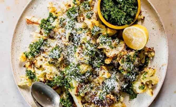 roasted cauliflower on a plate with cheese and chimichurri sauce