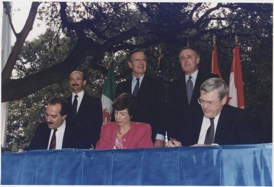 Lễ ký tắt NAFTA tại San Antonio, Texas, tháng 10/1992 Từ trái sang phải: (Đứng) Tổng thống Mexico Carlos Salinas de Gortari, Tổng thống Mỹ George H. W. Bush, Thủ tướng Canada Brian Mulroney. (Ngồi) Bộ trưởng Thương mại và Phát triển Công nghiệp Mexico Jaime Serra Puche, Đại diện Thương mại Mỹ Carla Hills, Bộ trưởng Thương mại Quốc tế Canada Michael Wilson.