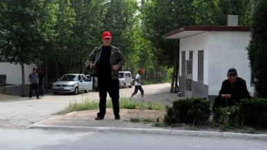 Công an mặc thường phục theo dõi lối vào làng Đông Sư Cổ. (AFP)