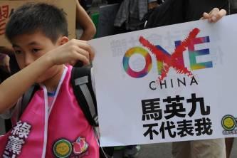 """Một cậu bé Đài Loan tại một cuộc biểu tình ở Đài Bắc cầm biển ghi dòng chữ tiếng Hoa: """"Mã Anh Cửu không đại diện cho tôi"""" hôm 7/11, ngày diễn ra cuộc gặp lịch sử ở Singapore (Ảnh: Sam Yeh/Agence France-Presse/Getty Images)"""