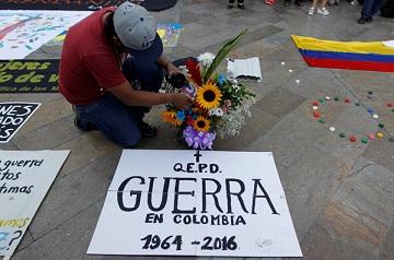 """Một người đàn ông chào mừng hòa ước đình chiến lịch sử giữa chính phủ Colombia và phiến quân FARC tại Quảng trường Botero ở Medellin, Colombia, hôm 23-6-2016. Tấm biển ghi """"Vĩnh biệt Chiến tranh ở Colombia 1964 - 2016"""". (Ảnh: Fredy Builes/Reuters)"""