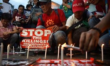 Những nhà hoạt động đốt nến trước một nhà thờ ở Manila trong lễ thắp nến tưởng niệm các nạn nhân của các vụ giết người không đúng quy trình tư pháp trong cuộc chiến chống ma túy của chính phủ. (Ảnh: Ted Aljibe/AFP/Getty Images)