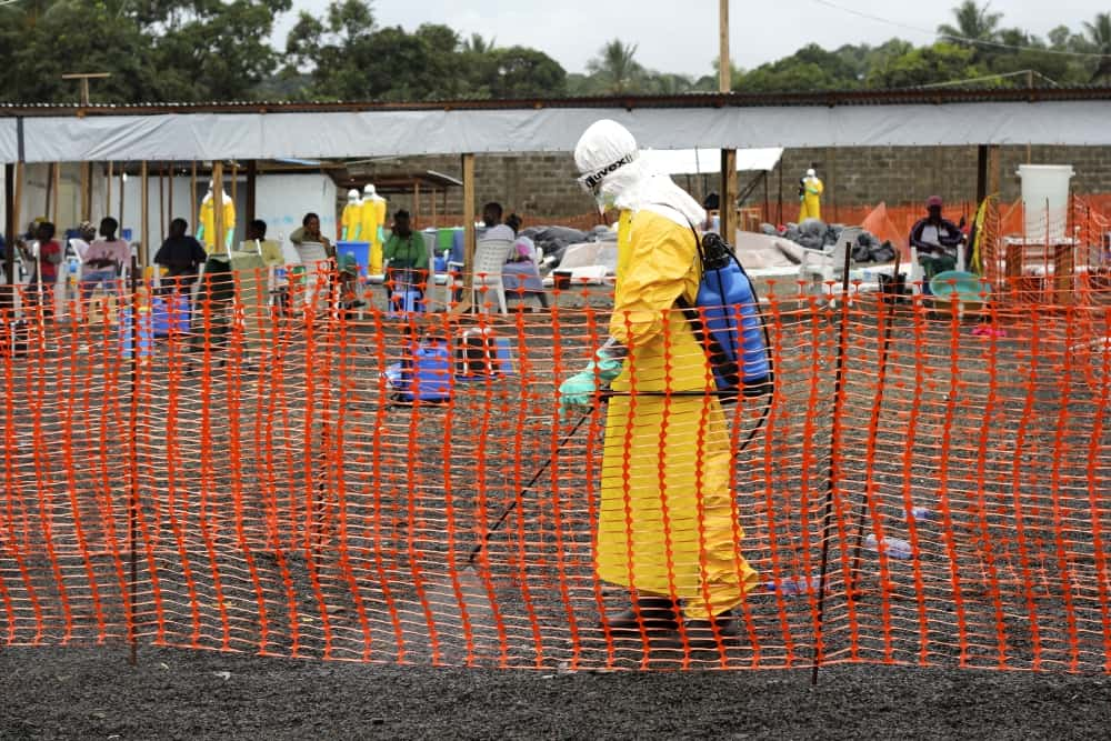 A hygienist disinfects the fence line at ELWA 3, MSF Ebola. Management centre in Monrovia. Photo: Caitlin Ryan/MSF