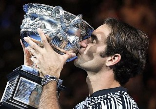 Switzerland's Roger Federer celebrates with the championship trophy during the awards ceremony after his victory against Spain's Rafael Nadal in the men's singles final on day 14 of the Australian Open tennis tournament in Melbourne on January 29, 2017. / AFP PHOTO / WILLIAM WEST / IMAGE RESTRICTED TO EDITORIAL USE - STRICTLY NO COMMERCIAL USE