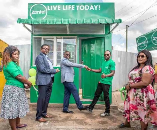 Zamtel Chief Commercial Officer Chibeza Ngoma does a foot shake with Joshua Mmembe, a trader at Chawama Market to celebrate the opening of a Zamtel Mini Service Centre