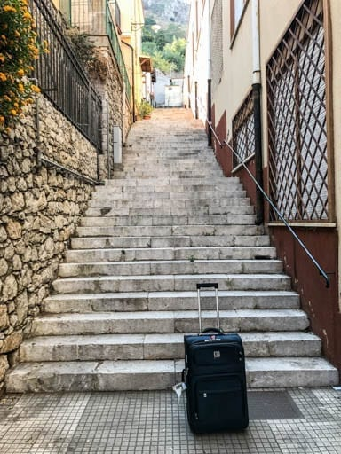 Suitcase at the base of the stairs