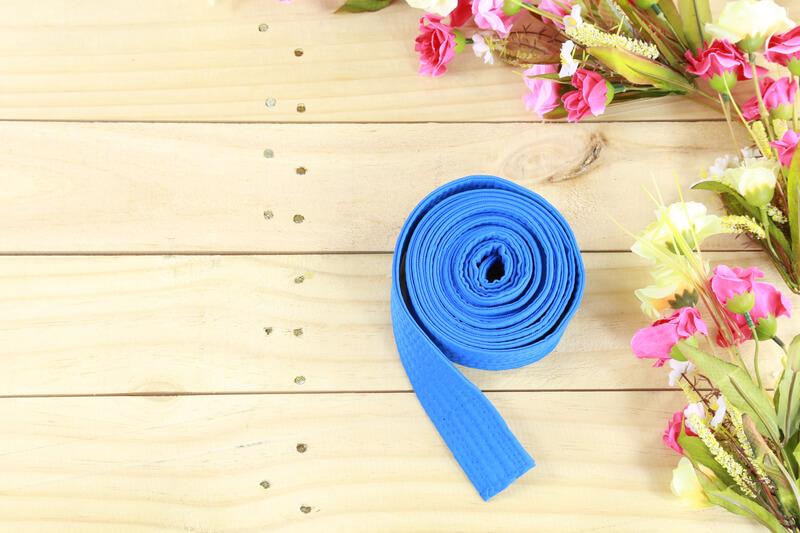 Budo Kai Martial Arts_ coiled blue belt on floor sprig of flowers on wood floor