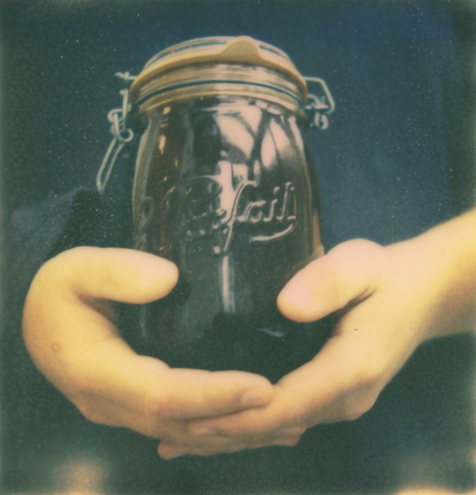 polaroid of hands holding a kilner jar containing cold brew coffee. copyright leonie wise