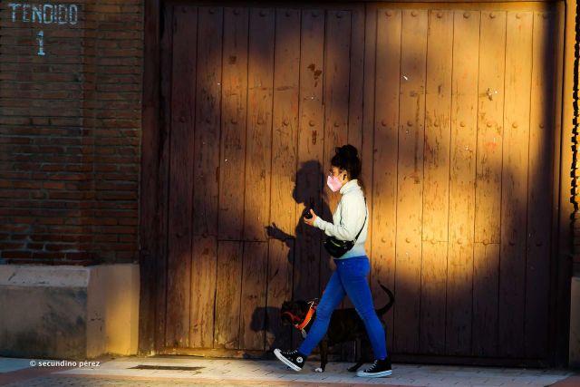 mujer con mascarilla pasea perro