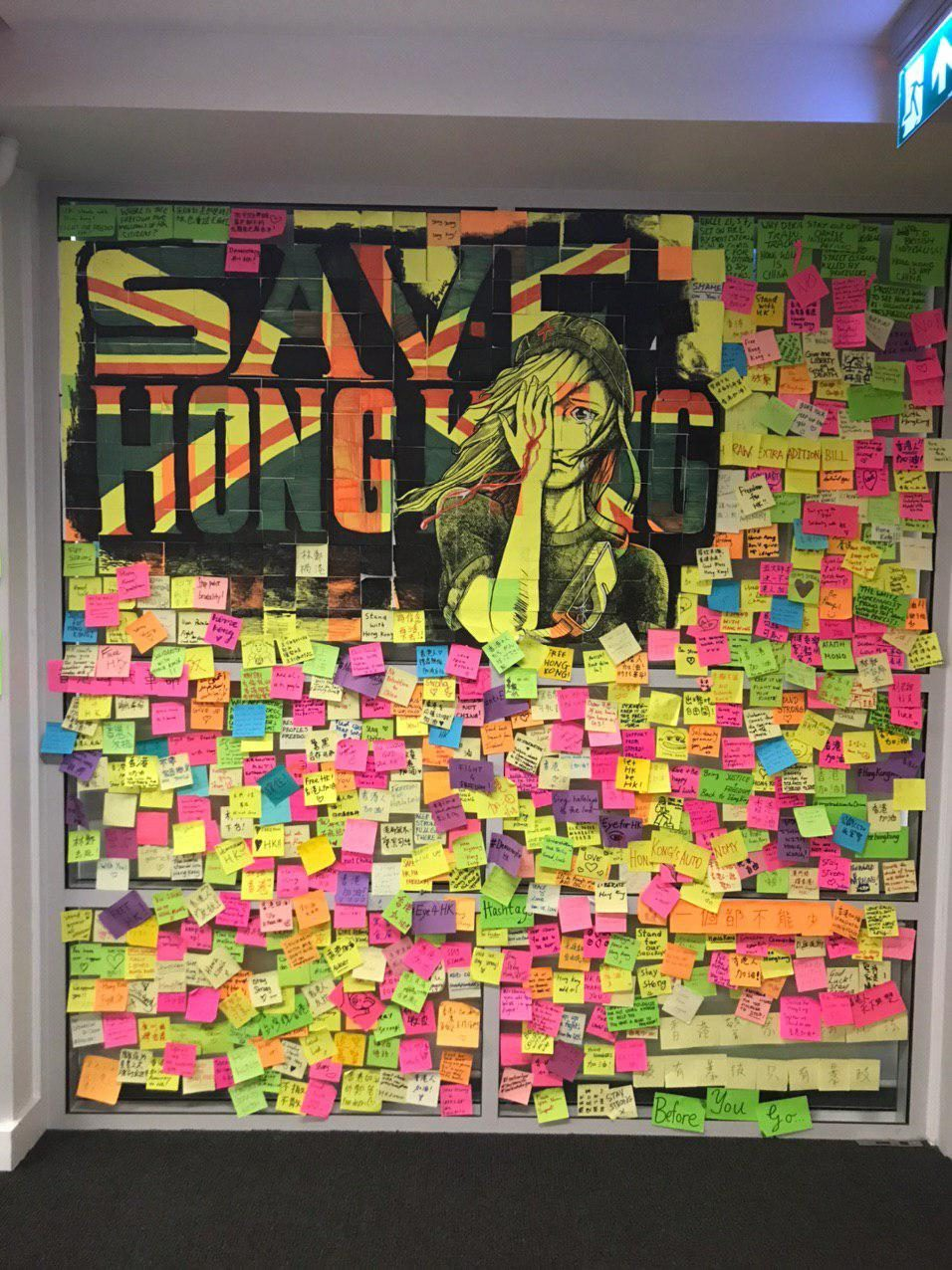 "A glass wall covered in post-its with messages written on them, under a mural of a woman covering her bleeding eye and the words ""Save Hong Kong"" backgrounded by a Union Jack."