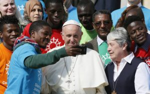 "Pope Francis poses for a selfie as he greets immigrants and representatives of Caritas Internationalis during his general audience in St. Peter's Square at the Vatican Sept. 27. Caritas Internationalis was kicking off its ""Share the Journey"" campaign in support of immigrants. At right is Sister Norma Pimentel, executive director of Catholic Charities of the Rio Grande Valley in Texas. (CNS photo/Paul Haring) See POPE-SHARE-JOURNEY Sept. 27, 2017."