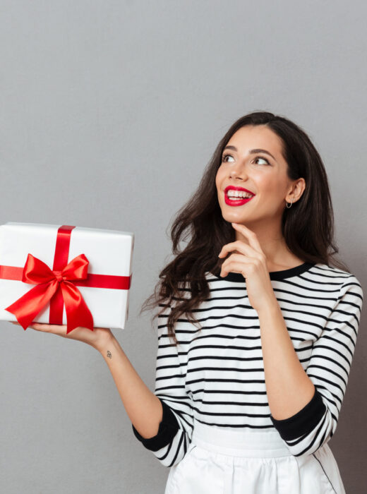 Portrait of a smiling woman holding gift box and looking away at copy space with hand on her chin isolated over gray background