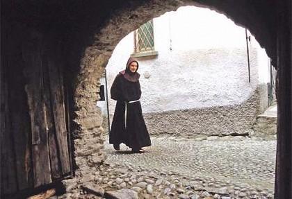 Frade franciscano numa velha rua medieval.