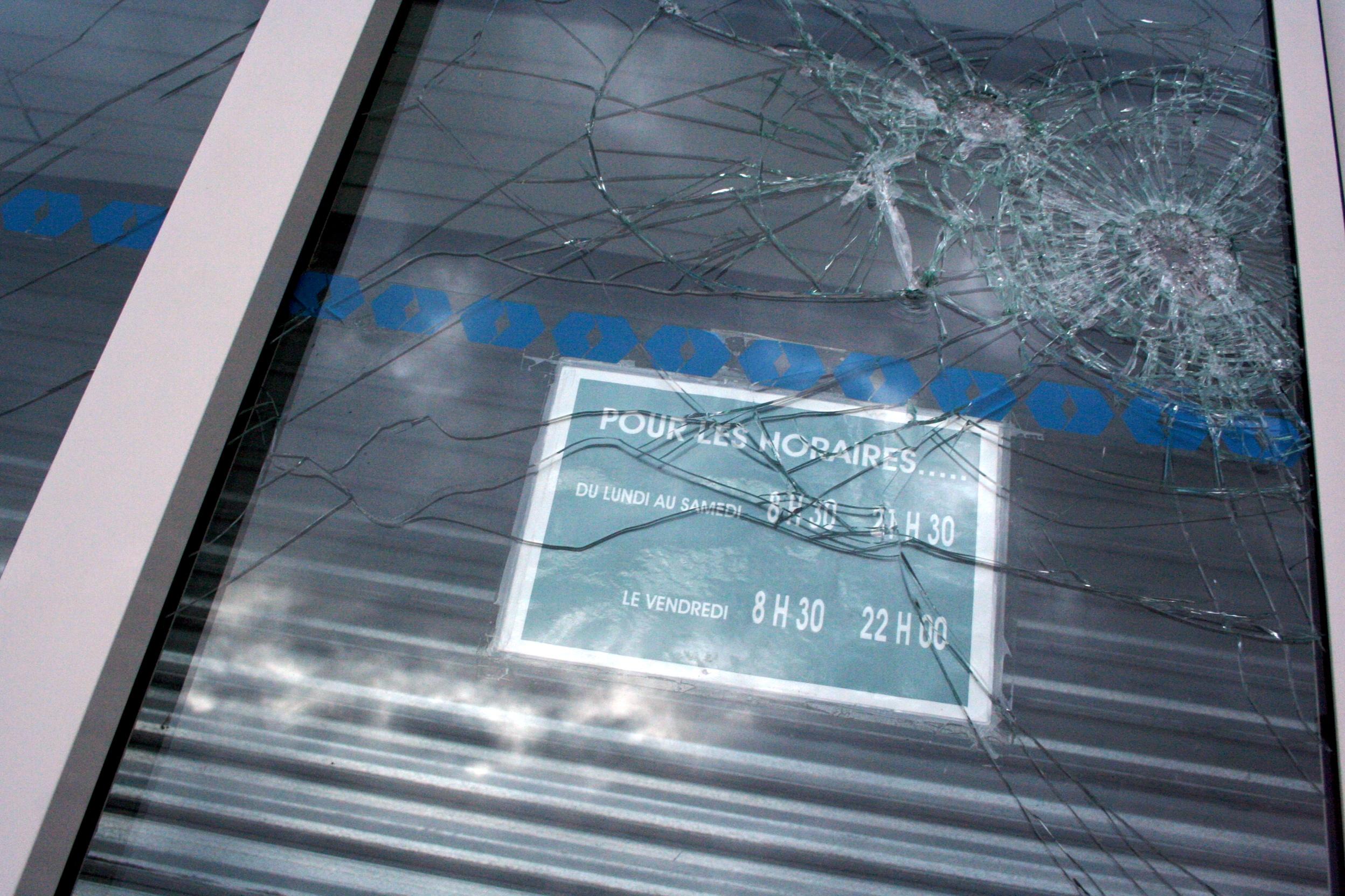Panneau horaires d'ouvertures sur une vitrine cassée