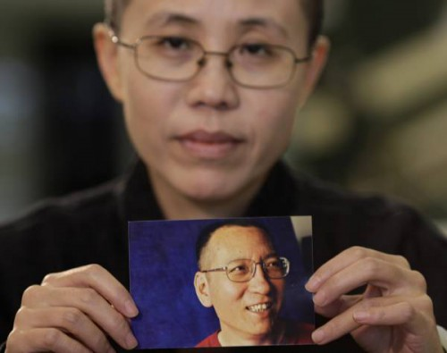 Liu Xia, the wife of Chinese dissident Liu Xiaobo, holds a photo of Liu Xiaobo during an interview in Beijing