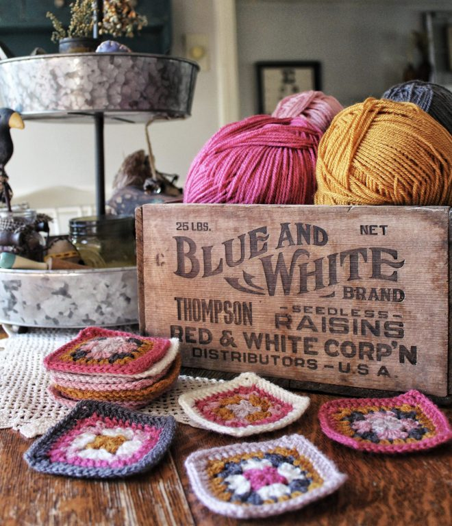 Colorful granny squares and beautiful yarn arranged in a rustic box.